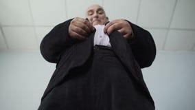 Essai masculin de poids excessif d'attacher un bouton sur sa veste, vue inférieure de gros homme banque de vidéos