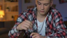 Essai somnolent d'écriture d'étudiant masculin, reposant à la maison la table, matière d'enseignement de sondage banque de vidéos