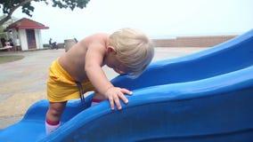 Essais d'enfant pour escalader la colline banque de vidéos