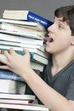 Essais de l'adolescence pour porter la pile mal équilibrée de manuels Image stock