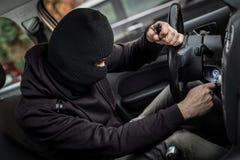 Essais de voleur de voiture pour mettre en marche la voiture Photographie stock