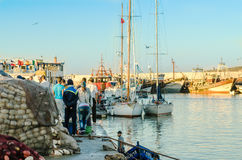 ESSAOUIRA, 10.2015 Μαρόκο-SEP: Λιμενική σκηνή προκυμαιών των ανθρώπων Ατμοσφαιρική εικόνα στο φως βραδιού με το χρώμα ηλιοβασιλέμ Στοκ φωτογραφίες με δικαίωμα ελεύθερης χρήσης