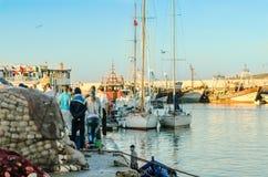 ESSAOUIRA Marocko-September 10,2015: Strandhamnplats av folk Atmosfärisk bild i aftonljus med solnedgångfärg Royaltyfria Foton