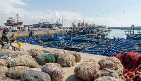 Essaouira, Marrocos - 15 de setembro de 2013: Barcos de pesca de madeira azuis ancorados no porto histórico com gaivotas e pescad Fotografia de Stock