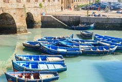 Fortress and blue fishing boats in Essaouira. Morocco Stock Photos