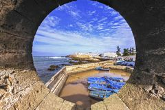 Essaouira Morocco Fishing Harbor. Fishing Harbor and Distant Mediterranean Landscape in Essaouira, Morocco viewed through Textured Porthole on old City Ramparts Royalty Free Stock Photo