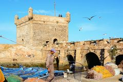 Fishing boats, gear and man with net on background of Castelo Real of Mogador. stock image