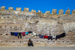 Essaouira, Morocco - January 8, 2017: Man with his clothes. A man is drying his clothes on the streets of Essaouira Royalty Free Stock Image