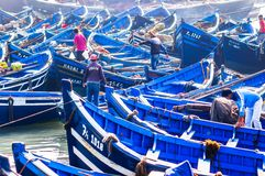 Essaouira, Morocco - November 05, 2015: Blue wooden rowing boats at the and fisher man in the port of Essaouira in Morocco royalty free stock photography