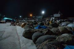 Essaouirahaven in Marokko De plaatselijke bevolking zit dichtbij de stapels van visnetten bij nacht royalty-vrije stock foto's