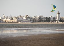 Early evening kite surfing as the sun starts to set over the ocean. Essaouria, Morocco - September 2017: Early evening kite surfing as the sun starts to set over stock photos