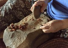 Making Argan Oil by Hand - smashing nuts open with a stone. Essaouria, Morocco - September 2017: Making Argan Oil by Hand - smashing nuts open with a stone stock photos