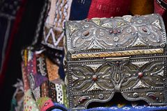 Ornate silver trinket box with colorful textiles on sale in a Moroccan Market. Essaouria, Morocco - September 2017: Ornate silver trinket box with colorful Royalty Free Stock Photo