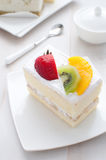 Essen der Frucht und des weißen Sahnekuchens Stockfotografie