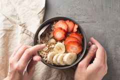 Essen der gesunden Frühstücksschüssel Muesli und frische Früchte in der keramischen Schüssel in Frau ` s Händen Sauberes Essen, n stockfoto