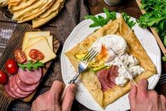 Essen des Frühstücks: kräuseln Sie galette, poschiertes Ei, Schinken, Avocado und Käse Stockfotografie