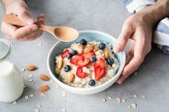 Essen des gesunden Frühstückshafermehlbreis mit frischen Beeren und Nüssen lizenzfreie stockfotos