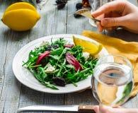 Essen des grünen Salats mit Arugula, der roten Rüben, des Ziegenkäses und der Olive oi Stockfotografie