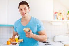 Essen des jungen Mannes des Frühstücks im Kücheneignungs-Morgen copysp stockfotos