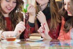 Essen des Kuchens, des trinkenden Tees u. der glücklichen Freundinnen Lizenzfreie Stockfotografie