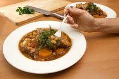 Essen des Lammeintopfgerichts Stockfoto