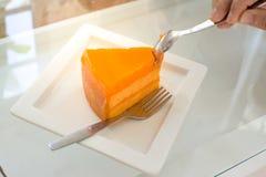 Essen des orange Kuchens Stockfotografie