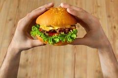 Essen des Schnellimbisses Hände, die Hamburger anhalten Gesichtspunkt Nutrit lizenzfreie stockbilder