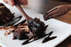 Essen des Schokoladenschokoladenkuchens mit hölzernem Löffel und Gabel Lizenzfreies Stockbild