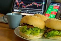 Essen des selbst gemachten Burgers beim Arbeiten mit einem Kerzenhalter-Diagramm auf Laptop für den Handel auf Börse stockbilder