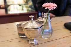 ESSEN, DEUTSCHLAND - 25. JANUAR 2017: Tischschmuck mit Rose färbte Blume in einem Café Lizenzfreies Stockfoto