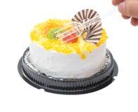 Essen eines leckeren Kuchens mit orange Kiwifruit und Schokolade der Traube mit Beschneidungspfad Stockbild