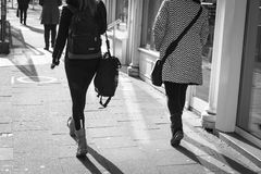 ESSEN, GERMANY - JANUARY 25, 2017: Two unidentifed ladies rush along the Ruettenscheider Strasse in their winter boots Royalty Free Stock Photo