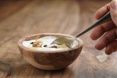 Essen mit selbst gemachtem Jogurt des Löffels mit muesli in der hölzernen Schüssel auf Holztisch Stockbild