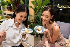 Essen schöne erwachsene berufstätige Frauen zwei Pfannkuchen lizenzfreie stockfotos