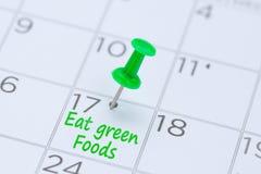 Essen Sie die grünen Nahrungsmittel, die auf einen Kalender mit einem grünen Stoßstift zu geschrieben werden stockbilder