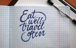 Essen Sie gut und reisen Sie häufig kalligraphischer Hintergrund Stockfotos