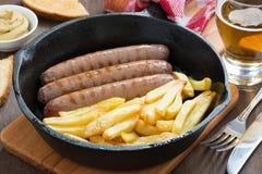 Essen Sie mit gegrillten Würsten, Pommes-Frites, Toast und Bier zu Mittag Lizenzfreie Stockfotos