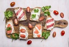 Essen Sie mit Sandwichen mit Salami und geräucherten roten Fischen mit hölzernen rustikalen Clo Draufsicht des Hintergrundes der  lizenzfreie stockbilder