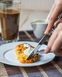 Essen Sie Quarkpfannkuchen mit Sauerrahm zum Frühstück, Hände Stockbild