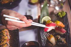 Essen Sie Sushi mit Essstäbchen lizenzfreie stockfotos