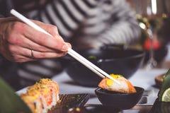 Essen Sie Sushi mit Essstäbchen stockfotos