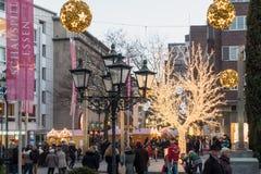 ESSEN TYSKLAND - DECEMBER 04, 2016: Oidentifierade individer går till och med en av de många upplysta shoppinggatorna av centret Royaltyfria Foton