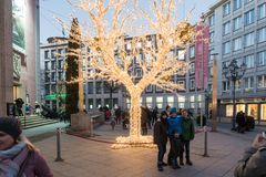 ESSEN TYSKLAND - DECEMBER 04, 2016: Oidentifierade ungar poserar för ett foto framme av ett upplyst träd Arkivbild