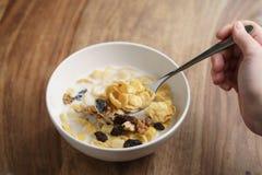 Essen von Corn Flakes mit Früchten und Nüssen in der weißen Schüssel Stockfotos