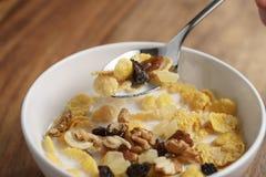 Essen von Corn Flakes mit Früchten und Nüssen in der weißen Schüssel Stockbilder