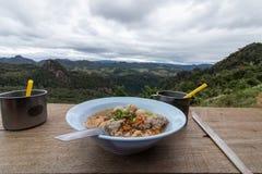 Essen von Nudeln auf dem Berg mit schönen Ansichten Lizenzfreies Stockfoto