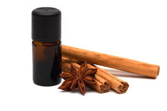 Essence with cinnamon sticks and anice. Essential oil with cinnamon sticks and anice on white background stock image