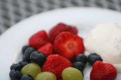 Essence of fantasy. A dish of fresh berries, strawberries, blueberries, grapes and whipped cream Royalty Free Stock Image