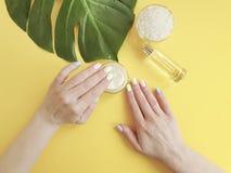 Essence femelle de manucure de mains, crème cosmétique, feuille molle de monstera, sur un fond jaune photographie stock libre de droits