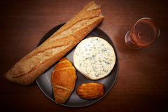 Essence of France. French blue cheese, baguette, croissant, madeleine and glass of wine on a table Stock Image